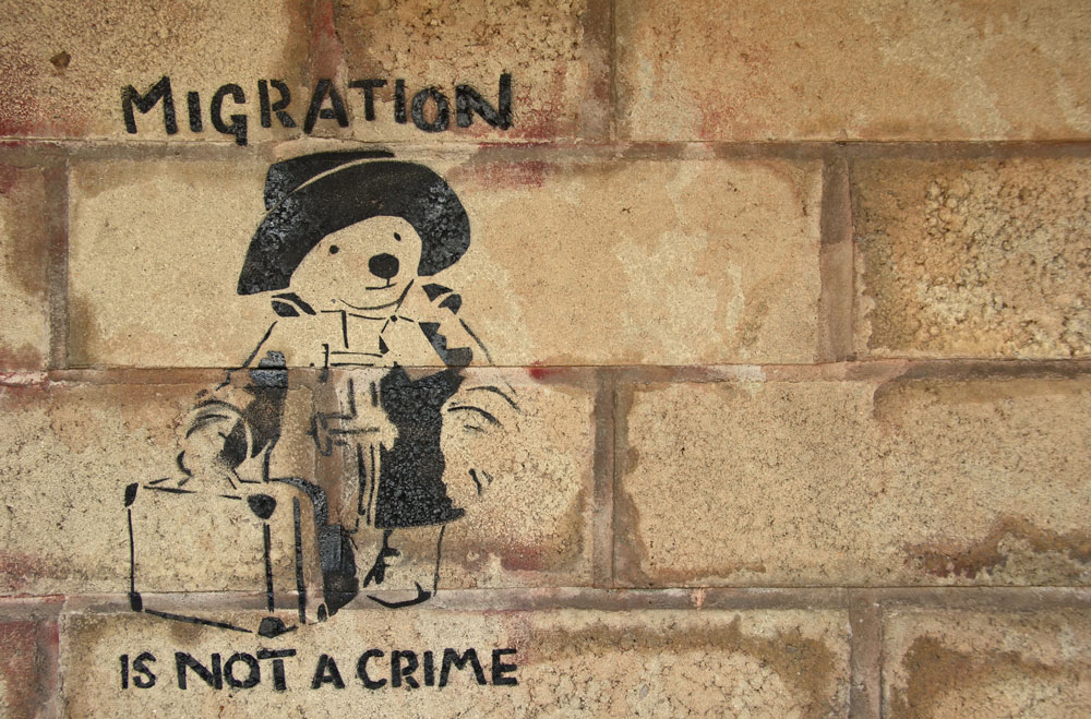 "Stencil graffiti of Paddington Bear with the slogan: ""migration is not a crime"""